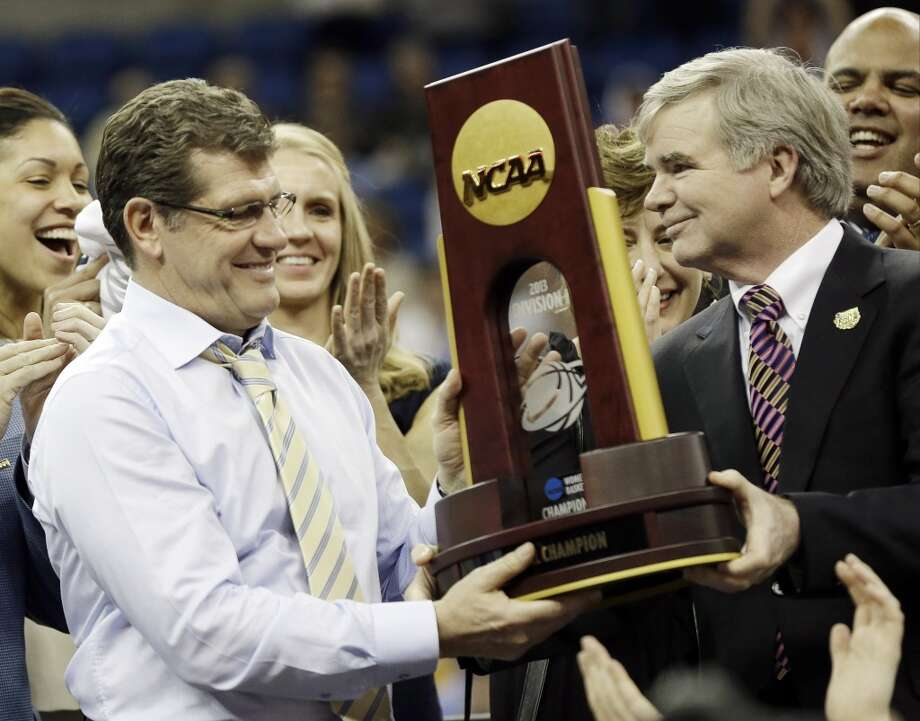Connecticut head coach Geno Auriemma receives the championship trophy of the women\'s Final Four of the NCAA college basketball tournament, Tuesday, April 9, 2013, in New Orleans. Connecticut defeated Louisville 93-60.