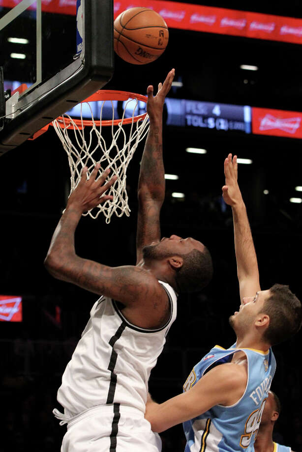 Brooklyn Nets\' Andray Blatche, left, goes up past Denver Nuggets\' Evan Fournier (94) during the first half of an NBA basketball game, Wednesday, Feb. 13, 2013, at Barclays Center in New York. Photo: Mary Altaffer, ASSOCIATED PRESS / AP2013