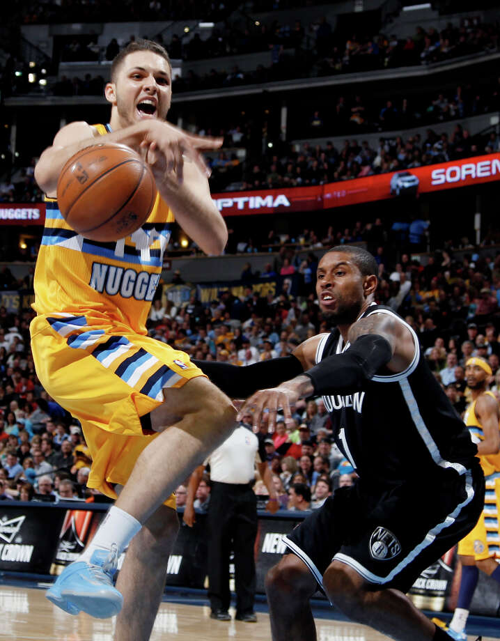 Denver Nuggets guard Evan Fournier, left, of France, loses control of the ball while driving the lane against Brooklyn Nets guard C.J. Watson during the fourth quarter of the Nuggets\' 109-87 victory in an NBA basketball game in Denver on Friday, March 29, 2013. Photo: David Zalubowski, Associated Press / AP