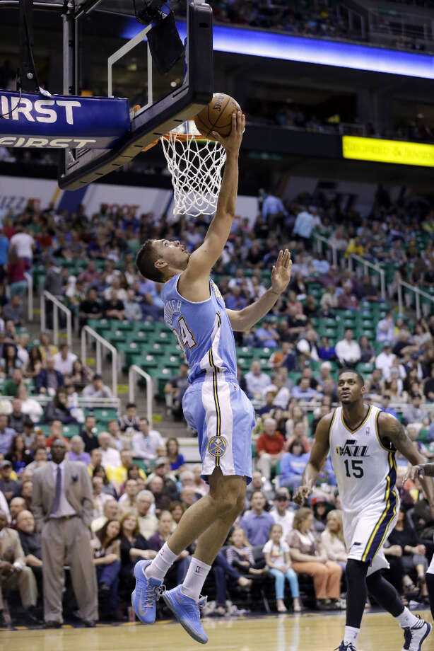 Denver Nuggets\' Evan Fournier, left, lays the ball up as Utah Jazz\'s Derrick Favors (15) looks on in the fourth quarter during an NBA basketball game Wednesday, April 3, 2013, in Salt Lake City. The Nuggets defeated the Jazz 113-96. Photo: Rick Bowmer, Associated Press / AP