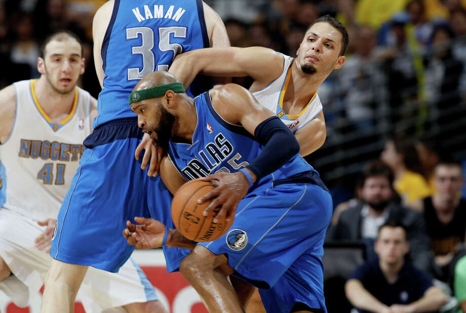 Dallas Mavericks guard Vince Carter, front, works the ball inside as Denver Nuggets guard Evan Fournier, of France, covers in the fourth quarter of the Nuggets\' 95-94 victory in an NBA basketball game in Denver on Thursday, April 4, 2013. Photo: David Zalubowski, Associated Press / AP