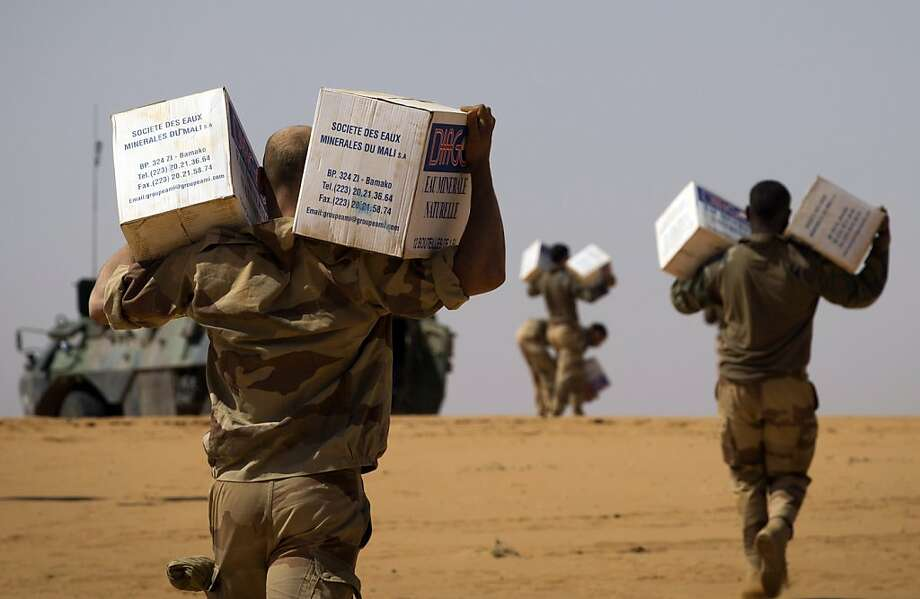"TOPSHOTS  French soldiers from the 126th Regiment Infantery carry boxes containing water bottles on April 8, 2013 some 105 kilometers North of Gao. A French force of 1,000 soldiers in a major offensive has swept a valley thought to be a logistics base for Al-Qaeda-linked Islamists near the Malian city of Gao. Operation Gustav, one of France's largest actions since its intervention against insurgents in January, will involve dozens of tanks, helicopters, drones and airplanes, said General Bernard Barrera, commander of the French land forces in Mali.  France is to start withdrawing its 4,000 troops from Mali at the end of April, and plans to leave a ""support force"" of 1,000 soldiers after elections promised for July.    AFP PHOTO /  JOEL SAGETJOEL SAGET/AFP/Getty Images Photo: Joel Saget, AFP/Getty Images"