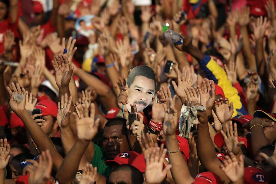 Supporters wave their hands as one of them holds a mask of Venezuela's acting President Nicolas Maduro during a campaign rally in Catia La Mar, Venezuela, Tuesday, April 9, 2013.  Maduro, the hand-picked successor of late President Hugo Chavez, is running for president against opposition candidate Henrique Capriles in the presidential election set for Sunday, April 14. (AP Photo/Ariana Cubillos) Photo: Ariana Cubillos, Associated Press