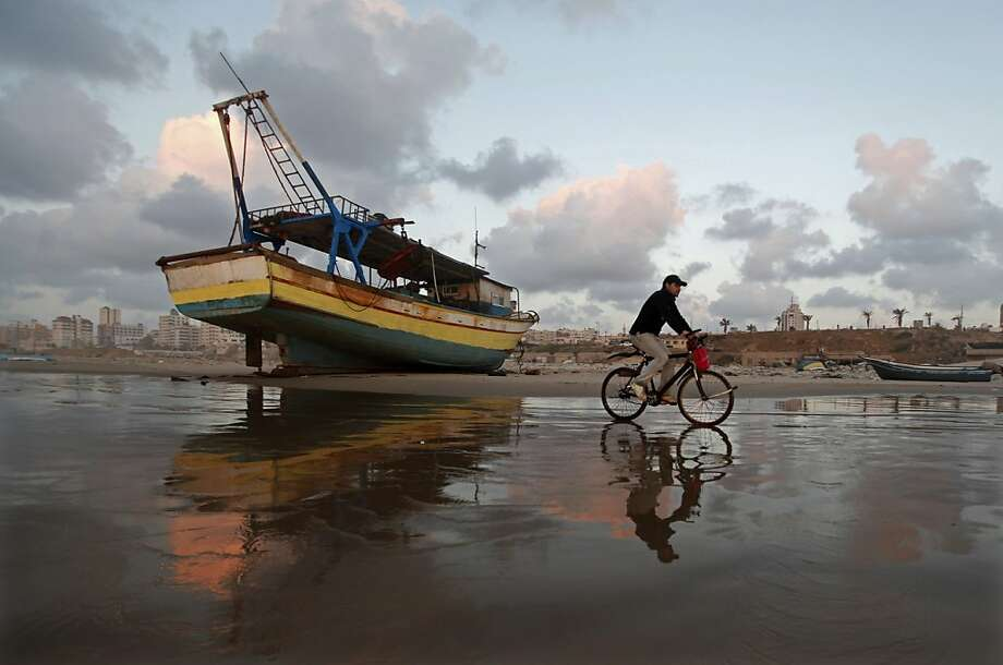 A Palestinian man rides a bicycle on the beach of Gaza City during sunset on Tuesday. April 9, 2013. (AP Photo/Hatem Moussa) Photo: Hatem Moussa, Associated Press