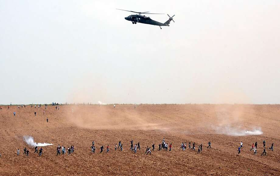 TOPSHOTS  An helicopter flies over a field as Turkish riot policemen and soldiers clash with protestors during a demonstration at Dicle University, in Diyarbakir, on April 9, 2013. Leftist Kurdish students protest after a clashing between left and right-wing groups at Dicle University. AFP PHOTO/MEHMET ENGINMEHMET ENGIN/AFP/Getty Images Photo: Mehmet Engin, AFP/Getty Images