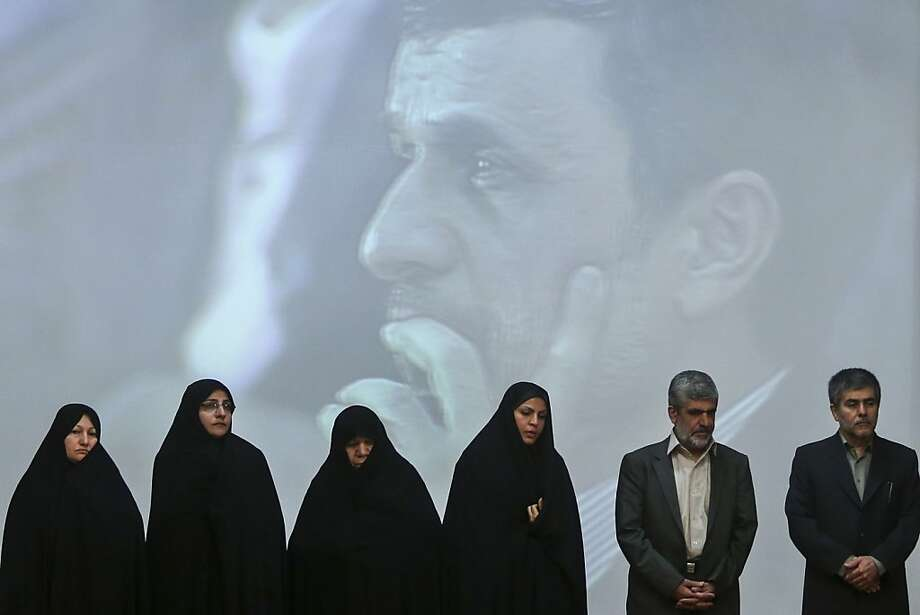 Family members of Iran's slain nuclear scientists and workers stand with the head of Iran's Atomic Energy Organization, Fereidoun Abbasi, right, in a ceremony marking Iran's National Day of Nuclear Technology, as President Mahmoud Ahmadinejad is seen on a giant screen behind them, in Tehran, Iran, Tuesday, April 9, 2013. Iran announced two key nuclear-related projects on Tuesday that expand the country's ability to extract and process uranium, which can be enriched for reactor fuel but also potentially for atomic weapons. (AP Photo/ISNA, Arash Khamoushi) Photo: Arash Khamoushi, Associated Press