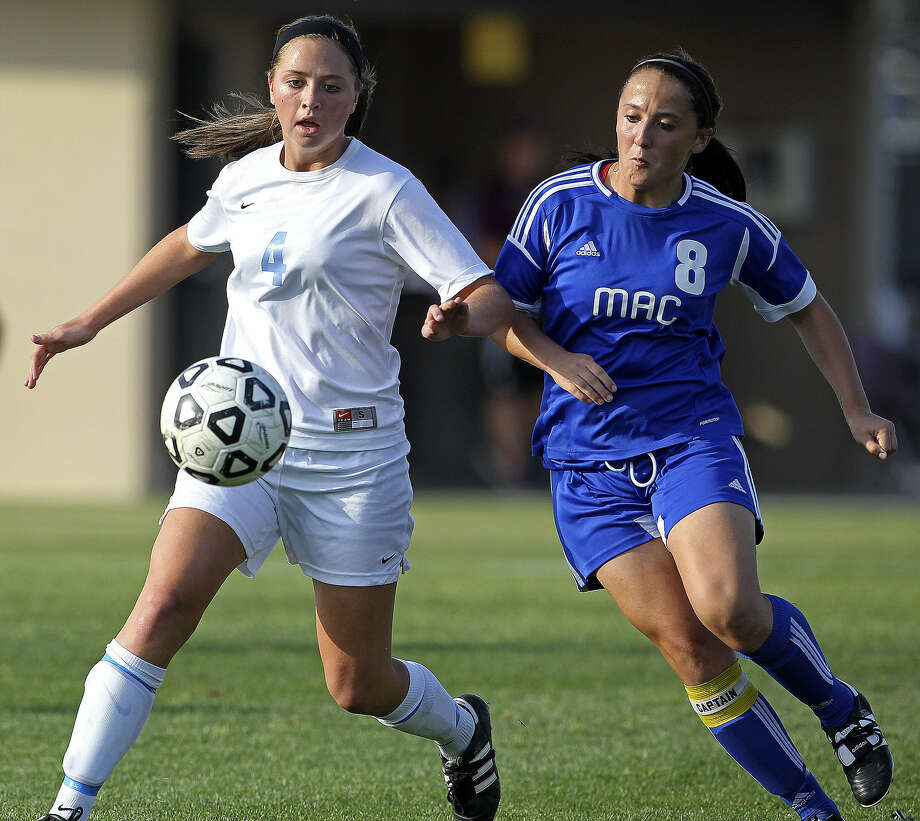 Johnson's Caitlin Schwartz (left) battles for the ball with MacArthur's Courtney Bertholf during the Jaguars' 3-0 playoff victory over their 26-5A rival. Schwartz scored Johnson's first goal.