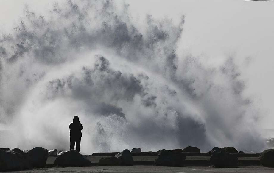 A person stands at the breakwall as waves crash at Cabrillo Beach in San Pedro, Calif. High winds rolled through Los Angeles Monday morning causing large surf. (AP Photo/Daily Breeze, Chuck Bennett) Photo: Chuck Bennett, Associated Press