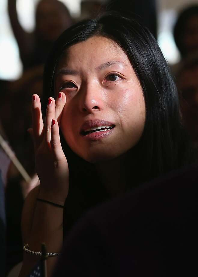 NEW YORK, NY - APRIL 09:  Chinese immigrant and new American citizen Yi Shu whipes a tear after taking the oath of citizenship at a naturalization ceremony on April 9, 2013 in New York City. Shu, who works at a hedge fund in New York City, was one of 15 immigrants from 13 countries who became U.S. citizens during the ceremony held at the Lower East Side Tenement Museum, which is dedicated to immigration history. Last year U.S. Citizenship and Immigration Services (USCIS), naturalized more than 676,000 new U.S. citizens and more than 84,000 of those were in the New York  district.  (Photo by John Moore/Getty Images) Photo: John Moore, Getty Images