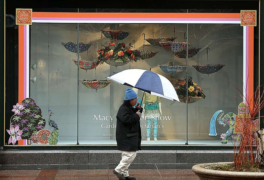 Anthony Xiong used an umbrella to protect himself from sleet and rain as he walks past a colorful display window on Nicollet Mall in Minneapolis TUESDAY APRIL 9, 2013.  (AP Photo/The Star Tribune, Jim Gehrz)  MANDATORY CREDIT; ST. PAUL PIONEER PRESS OUT; MAGS OUT; TWIN CITIES TV OUT Photo: Jim Gehrz, Associated Press