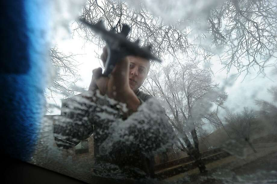 Connor Majerus chips away ice off his windshield along Menlo Avenue and 24th Street in Sioux Falls, S.D. on Tuesday, April 9, 2013. An early spring storm walloped South Dakota early Tuesday with rain, thunder, heavy snow and strong winds, and cutting power to thousands of homes and businesses. (AP Photo/The Argus Leader, Jay Pickthorn)  NO SALES Photo: Jay Pickthorn, Associated Press