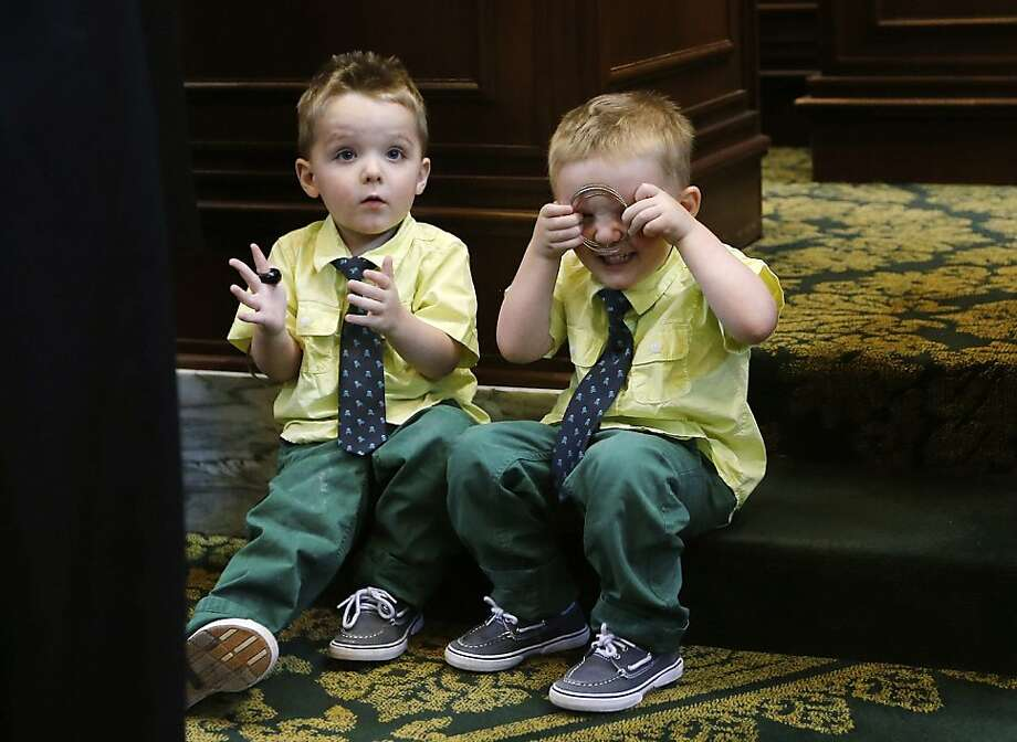 Three-year-old Landon Kerchee, left, applauds, and Maddox Kerchee, right, plays, on the floor of the Oklahoma House as their father, former soldier Jeff Kerchee, is awarded the purple heart, on appreciation day for the  Oklahoma National Guard's 45th Infantry Division in the Oklahoma Legislature, in Oklahoma City, Tuesday, April 9, 2013. Kerchee, of Edmond, Okla., is being awarded the Purple Heart Medal for wounds received on February 11, 2007, while deployed with the 1345th Transportation Company, Oklahoma Army National Guard. (AP Photo/Sue Ogrocki, Pool) Photo: Sue Ogrocki, Associated Press
