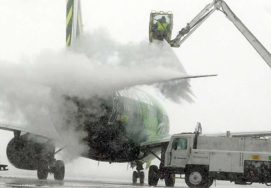 A truck sprays deicing fluid onto an airplane preparing for takeoff during a storm that brought some snow and a fast plunge in temperature overnight to Denver International Airport, Tuesday April 9, 2013. Despite some cancellations, over one thousand planes have been deiced and flown out of DIA since 6am Tuesday, according to the DIA spokesman. (AP Photo/Brennan Linsley) Photo: Brennan Linsley, Associated Press