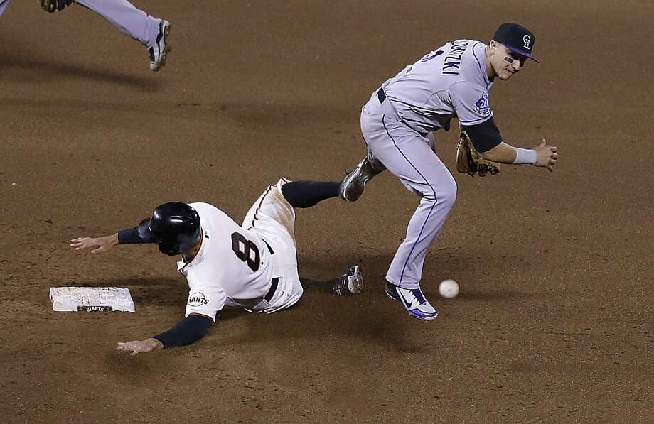 Colorado Rockies shortstop Troy Tulowitzki (2) throws to first base after forcing out San Francisco Giants' Hunter Pence (8) at second base on a double play hit into by Brandon Belt during the sixth inning of a baseball game in San Francisco, Tuesday, April 9, 2013. (AP Photo/Jeff Chiu) Photo: Jeff Chiu, Associated Press