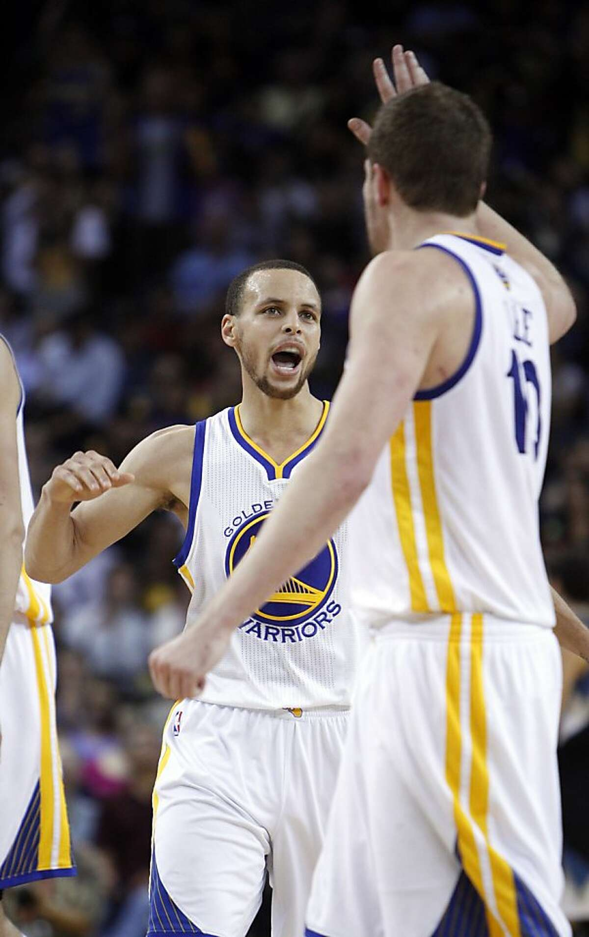 Stephen Curry, left, and David Lee, right, react after Curry hit a three-point shot in the second half. The Golden State Warriors played the Minnesota Timberwolves at Oracle Arena in Oakland, Calif., on Tuesday, April 9, 2013, winning the game 105-89 and clinching a playoff berth for the first time since 2007.