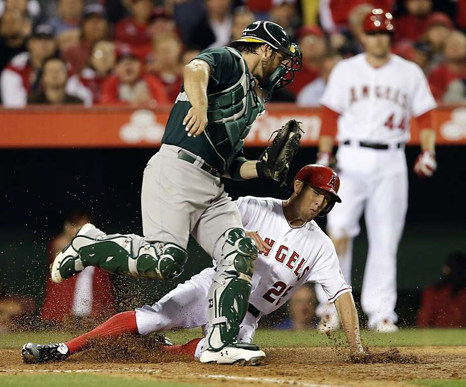 Los Angeles Angels' Peter Bourjos, bottom, is tagged out by Oakland Athletics catcher Derek Norris while trying to score on a hit by Josh Hamilton during the fourth inning of a baseball game in Anaheim, Calif., Tuesday, April 9, 2013. (AP Photo/Chris Carlson) Photo: Chris Carlson, Associated Press