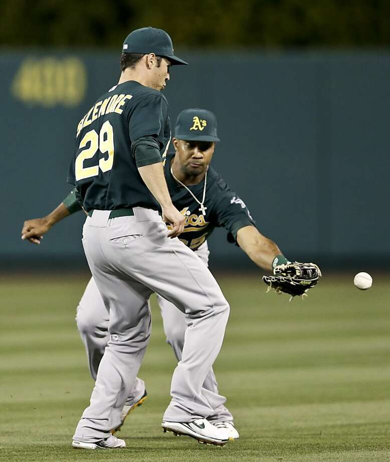 Oakland Athletics center fielder Chris Young, right, and first baseman Scott Sizemore can't get a glove on a base hit by Los Angeles Angels' Mike Trout during the fourth inning of a baseball game in Anaheim, Calif. Tuesday, April 9, 2013. (AP Photo/Chris Carlson) Photo: Chris Carlson, Associated Press