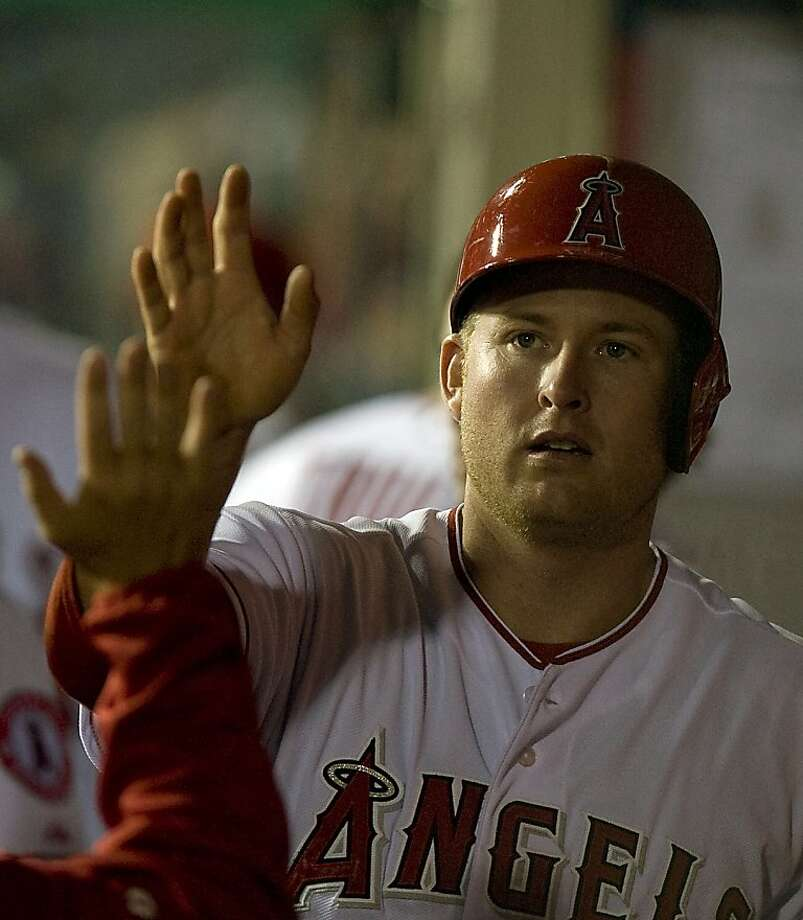 The Los Angeles Angels' Mark Trumbo Mark Trumbo is greeted inside the dugout after scoring in the third inning against the Oakland Athletics at Angel Stadium in Anaheim, California, on Tuesday, April 9, 2013. (Rose Palmisano/Orange County Register/MCT) Photo: Rose Palmisano, McClatchy-Tribune News Service