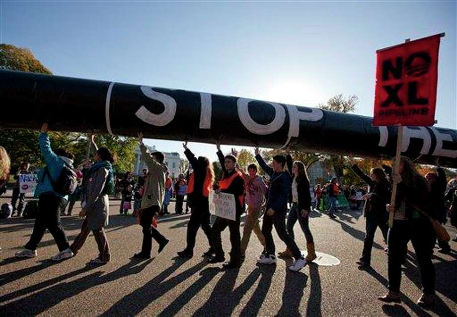 Demonstrators march with a replica of a pipeline during a protest against the Keystone XL Pipeline outside the White House on Sunday, Nov. 6, 2011, in Washington.  (AP Photo/Evan Vucci) Photo: Evan Vucci, ASSOCIATED PRESS / AP2011