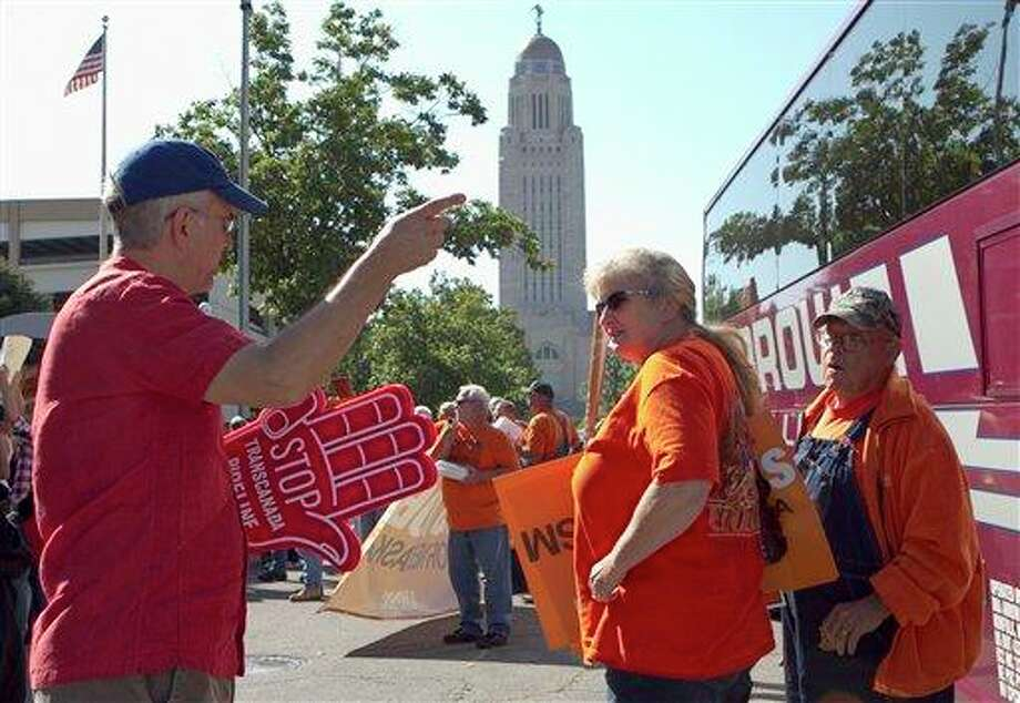 Demonstrators for the Keystone XL pipeline, right, and a demonstrator against the pipeline meet outside Pershing Auditorium near the state Capitol in Lincoln, Neb., Tuesday, Sept. 27, 2011, before a hearing on the pipeline. Opponents of the pipeline that would carry tar sands oil from Canada to Texas through the sandhills of Nebraska expressed concern about the pipeline's effect on the Ogallala Aquifer, a vast subterranean reservoir that spans a large swath of the Great Plains and provides water to eight states, while supporters of the pipeline, which include labor unions and business groups, spoke of jobs and development and energy security. (AP Photo/Nati Harnik) Photo: Nati Harnik, AP