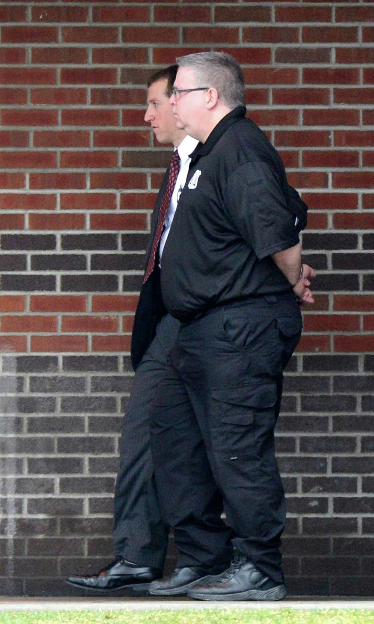 Albany County corrections officer James Cerniglia is escorted out of Albany County Jail after being arrested Wednesday morning, April 10, 2013, in Colonie, N.Y. Cerniglia is accused of running a Capital Region bookmaking ring in which bets and payoffs were routinely taking place at the jail. (Skip Dickstein/Times Union)