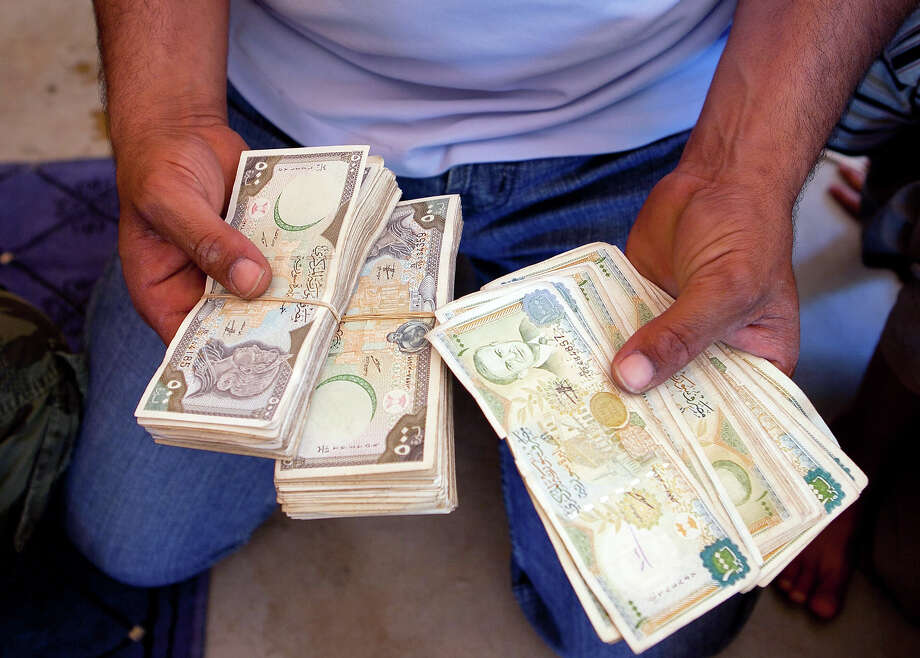 A  fighter from the rebel Free Syrian Army (FSA) counts wads of cash - Syrian pounds - before buying weapons and ammunition from a seller in Idlib province on July 4, 2012. US Secretary of State Hillary Clinton urged the UN to use the threat of sanctions to force change in Syria on July 6, 2012, as President Bashar al-Assad was rocked by the defection of one of his most senior generals. Photo: AFP, AFP/Getty Images / 2012 AFP