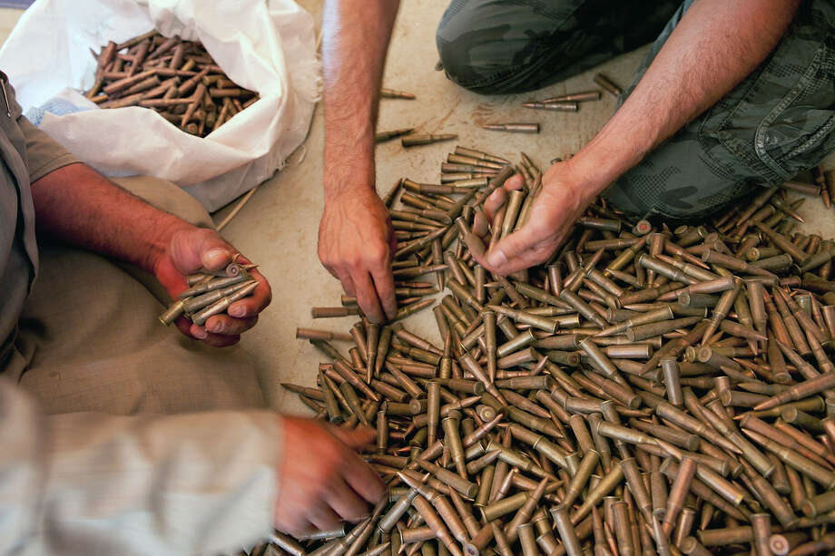 Fighters from the Free Syrian Army buy AK-47 bullets from a weapons seller in Idlib province on July 4, 2012. US Secretary of State Hillary Clinton urged the UN to use the threat of sanctions to force change in Syria on July 6, 2012, as President Bashar al-Assad was rocked by the defection of one of his most senior generals. Photo: AFP, AFP/Getty Images / 2012 AFP