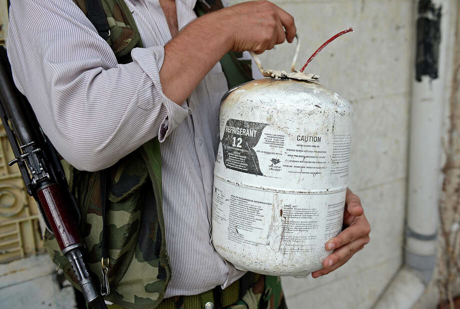A Syrian rebel carries a homemade bomb in the northern city of Aleppo on October 8, 2012. A string of rebel bastions across Syria was rocked by regime shelling and clashes, as several army checkpoints also came under attack, with more than 60 people killed nationwide, a rights group said. Photo: TAUSEEF MUSTAFA, AFP/Getty Images / 2012 AFP