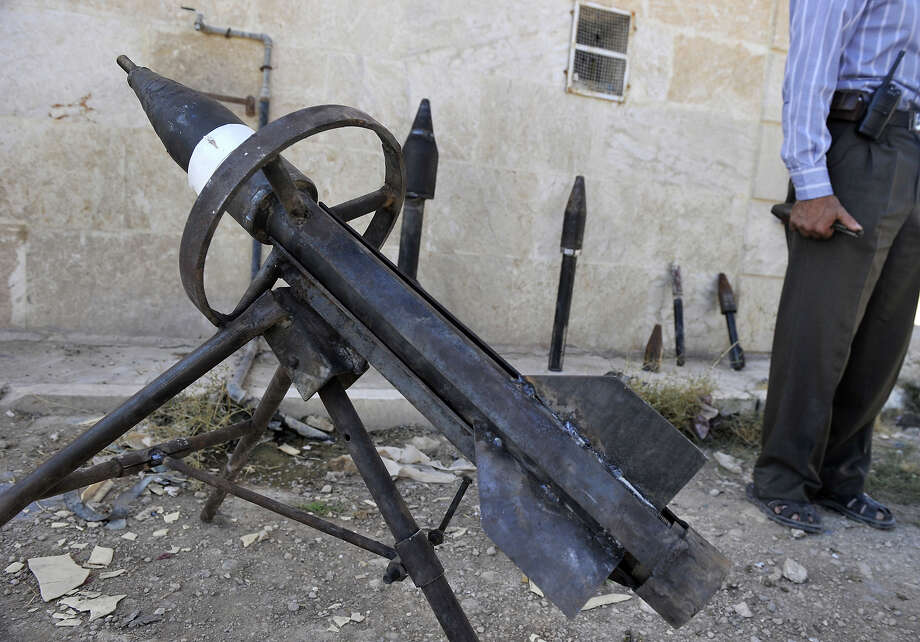Rebel arms maker Abu al-Fadhel shows off a row of homemade weapons including a hand-grenade, a portable rocket-launcher, and various rockets with explosive warheads at a location in Aleppo province on October 17, 2012. Lightly-armed Syrian rebels who face the warplanes, artillery and tanks of President Bashar al-Assad's forces have turned to making their own weapons to fill major gaps in their armories. Photo: TAUSEEF MUSTAFA, AFP/Getty Images / 2012 AFP