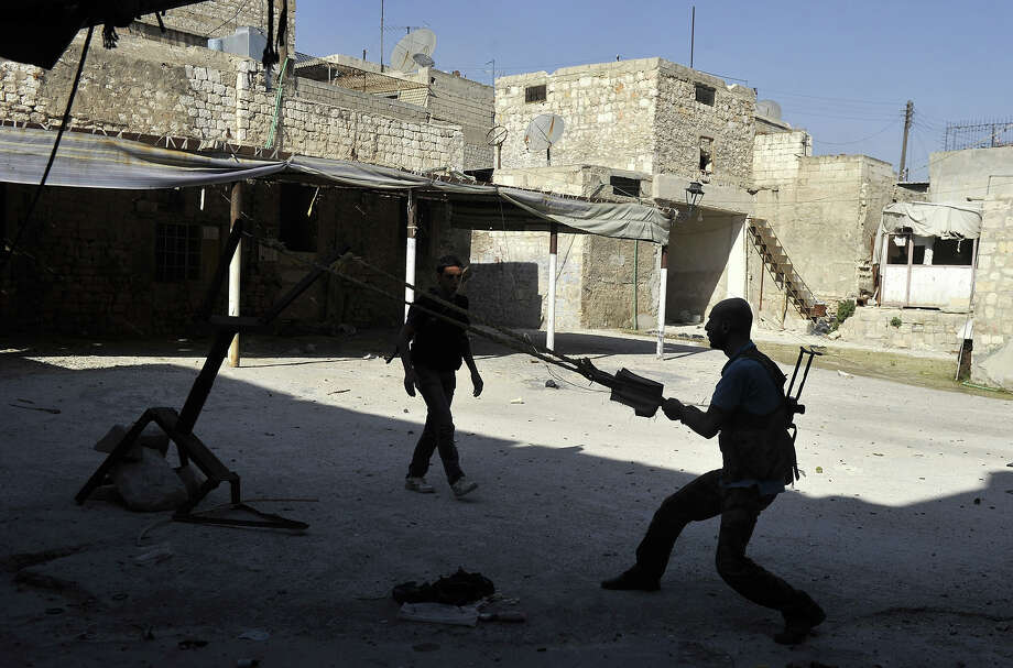 A Syrian rebel readies to fire a bomb using a homemade slingshot in the northern city of Aleppo on October 16, 2012. Lightly-armed Syrian rebels who face the warplanes, artillery and tanks of loyalists have turned to making their own weapons, even rigging a video game controller to fire mortar rounds. Photo: TAUSEEF MUSTAFA, AFP/Getty Images / 2012 AFP