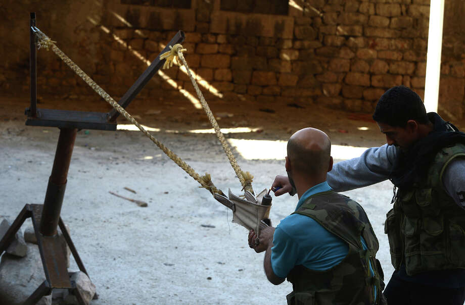 Syrian rebels prepare to fire a bomb using a homemade slingshot in the northern city of Aleppo on October 16, 2012. Lightly-armed Syrian rebels who face the warplanes, artillery and tanks of loyalists have turned to making their own weapons, even rigging a video game controller to fire mortar rounds. Photo: TAUSEEF MUSTAFA, AFP/Getty Images / 2013 AFP