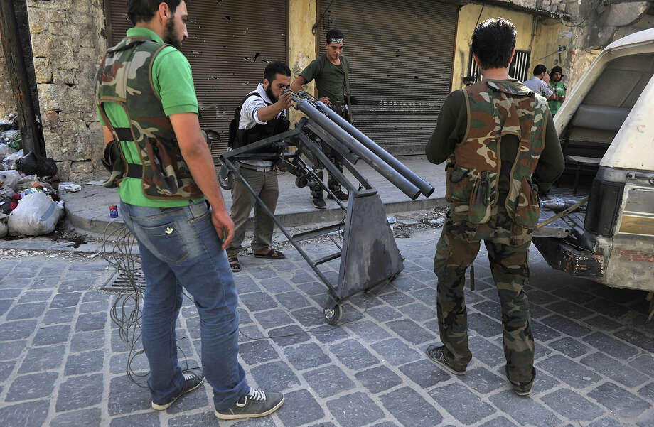 Syrian rebels adjust a homemade mortar launcher in the northern city of Aleppo on October 16, 2012. Lightly-armed Syrian rebels who face the warplanes, artillery and tanks of loyalists have turned to making their own weapons, even rigging a video game controller to fire mortar rounds. Photo: TAUSEEF MUSTAFA, AFP/Getty Images / 2012 AFP