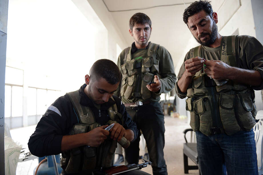 Rebel fighters prepare homemade hand grenades during fighting against pro-Syrian government troops in the Bustan al-Bashar district of the northern Syrian city of Aleppo, on October 27, 2012.  Syrian rebels clashed with Kurdish militia in the northern city of Aleppo, leaving 30 dead and around 200 captured, a watchdog said, sparking fears of a new front in an already fractured country. Photo: PHILIPPE DESMAZES, AFP/Getty Images / 2012 AFP