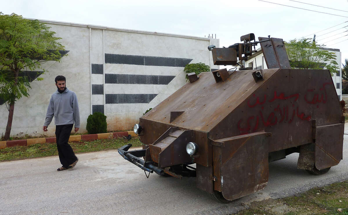 A Syrian rebel walks past Sham II, a homemade armored vehicle made by the rebels' Al-Ansar brigade, in Bishqatin, 4 kms west of Aleppo, on December 8, 2012. From a distance it looks rather like a big rusty metal box but closer inspection reveals the latest achievement of Syrian rebels: a homemade armoured vehicle waiting to be deployed. Sham II, named after ancient Syria, is built from the chassis of a car and touted by rebels as