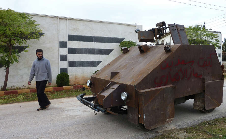 "A Syrian rebel walks past Sham II, a homemade armored vehicle made by the rebels' Al-Ansar brigade, in Bishqatin, 4 kms west of Aleppo, on December 8, 2012. From a distance it looks rather like a big rusty metal box but closer inspection reveals the latest achievement of Syrian rebels: a homemade armoured vehicle waiting to be deployed. Sham II, named after ancient Syria, is built from the chassis of a car and touted by rebels as ""100 percent made in Syria."" Photo: AFP, AFP/Getty Images / 2012 AFP"