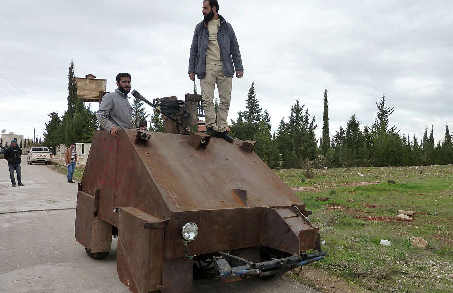 "Syrian rebels stand atop Sham II, a homemade armored vehicle made by the rebels' Al-Ansar brigade, in Bishqatin, 4 kms west of Aleppo, on December 8, 2012. From a distance it looks rather like a big rusty metal box but closer inspection reveals the latest achievement of Syrian rebels: a homemade armoured vehicle waiting to be deployed. Sham II, named after ancient Syria, is built from the chassis of a car and touted by rebels as ""100 percent made in Syria."" Photo: AFP, AFP/Getty Images / 2012 AFP"