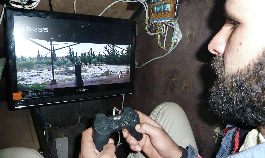"""A Syrian rebel uses a control stick to activate the machine-gun of Sham II, a homemade armoured vehicle made by the rebels' Al-Ansar brigade, in Bishqatin, 4 kms west of Aleppo, on December 8, 2012. From a distance it looks rather like a big rusty metal box but closer inspection reveals the latest achievement of Syrian rebels: a homemade armored vehicle waiting to be deployed. Sham II, named after ancient Syria, is built from the chassis of a car and touted by rebels as """"100 percent made in Syria."""" Photo: AFP, AFP/Getty Images / 2013 AFP"""