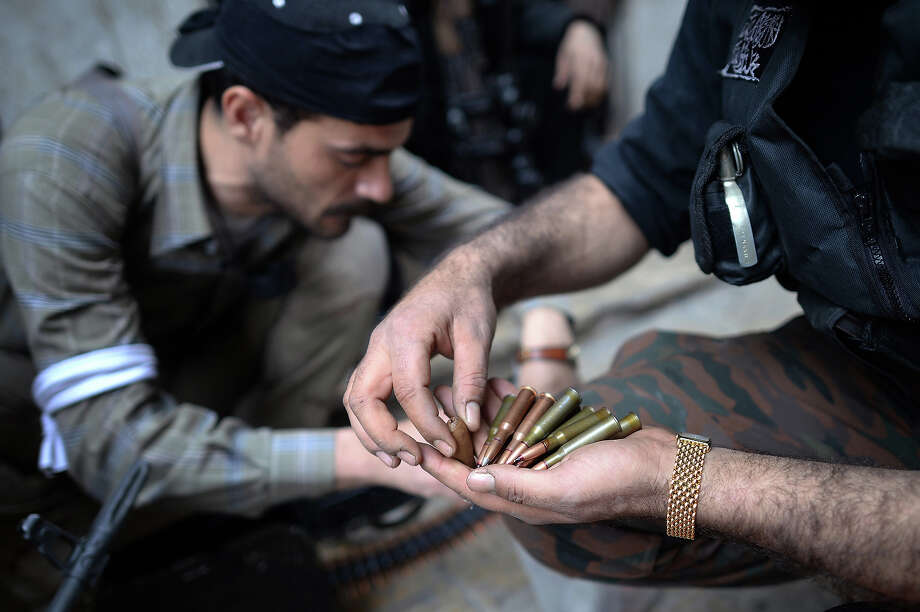 Rebel fighter load their weapons in the Sheikh Maqsud neighborhood in Aleppo on April 4, 2013. The UN says more than 70,000 people have been killed in a spiraling war that broke out after the army unleashed a crackdown on a peaceful revolt which morphed into an armed revolt. Photo: DIMITAR DILKOFF, AFP/Getty Images / 2013 AFP
