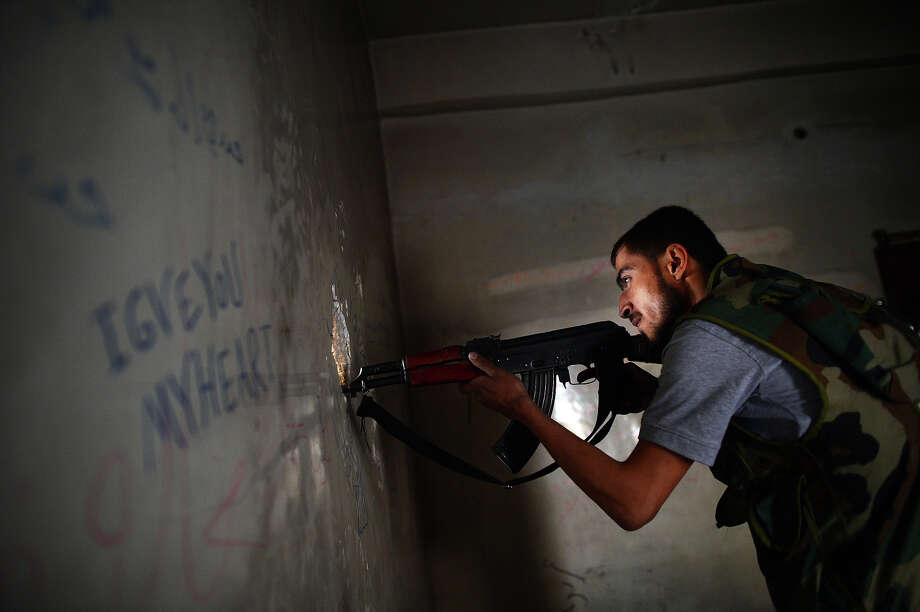 A Syrian rebel observes the movement of regime forces as he takes position inside a building in the Saif al-Dawla district of the northern Syrian city of Aleppo on April 5, 2013. The UN is hiking its estimates of people trapped in Syria after fleeing their homes, saying some four million are now displaced inside the country and in dire need of international help. Photo: DIMITAR DILKOFF, AFP/Getty Images / 2013 AFP