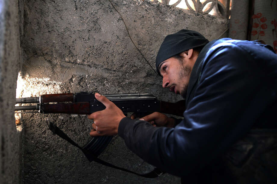 A Syrian rebel fighter points his weapon towards the positions of Syrian government forces in the Saladin district of the northern Syrian city of Aleppo on April 8, 2013. Photo: DIMITAR DILKOFF, AFP/Getty Images / 2013 AFP