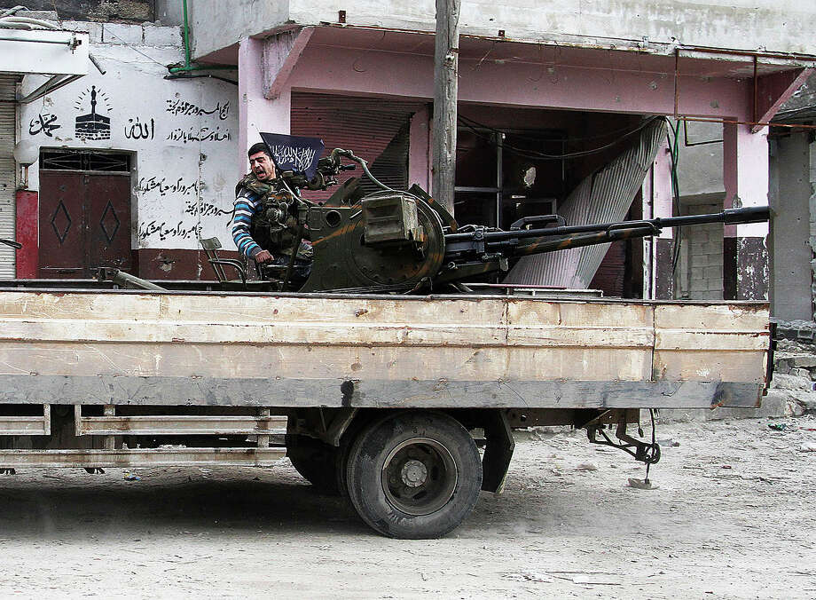 In this Friday February 8, 2013 photo, a Free Syrian Army fighter sits behind an anti-aircraft weapon in Aleppo, Syria. Syrian rebels brought their fight within a mile of the heart of Damascus on Friday, seizing army checkpoints and cutting a key highway with a row of burning tires as they pressed their campaign for the heavily guarded capital, considered the likely endgame in the nearly 2-year-old civil war. Photo: Abdullah Al-Yassin, ASSOCIATED PRESS / AP2013