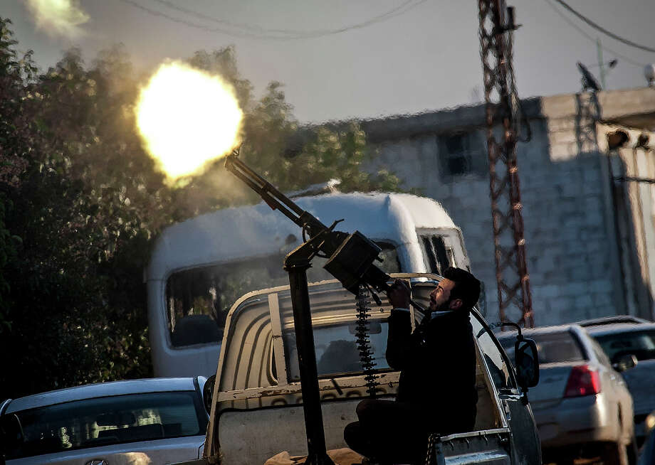 In this Saturday, Dec. 15, 2012 photo, A Free Syrian Army fighter fires a weapon during heavy clashes with government forces at a academy besieged by rebels north of Aleppo, Syria. Photo: Narciso Contreras, ASSOCIATED PRESS / AP2012