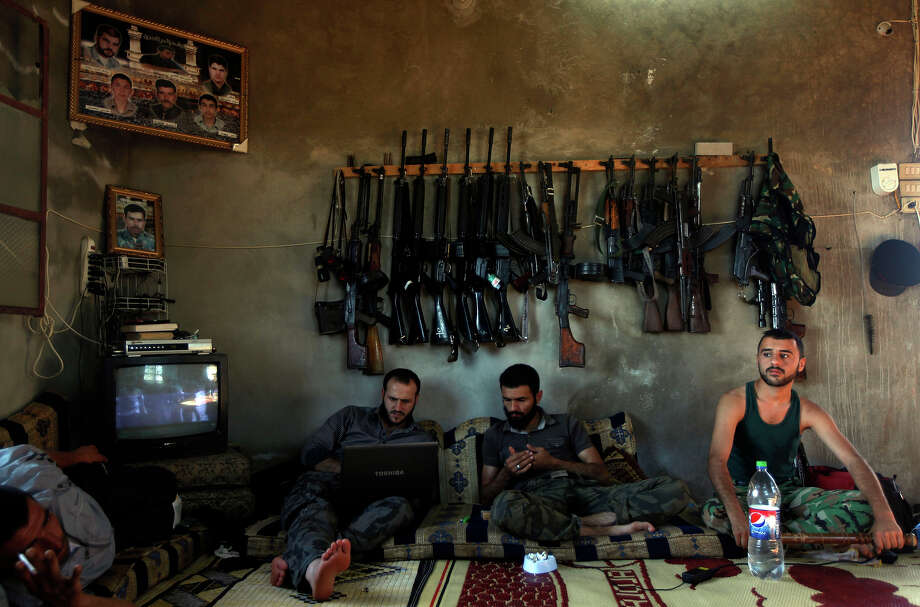 Free Syrian Army fighters sit in a house on the outskirts of Aleppo, Syria. During two weeks with rebels in northern Syria, three Associated Press journalists found more than 20 rebel groups who often destroy government army posts and convoys but lack the weapons and unity to do more than gradually chip away at the regime of President Bashar Assad — a recipe for a long, bloody insurgency. Photo: Khalil Hamra, ASSOCIATED PRESS / AP2012