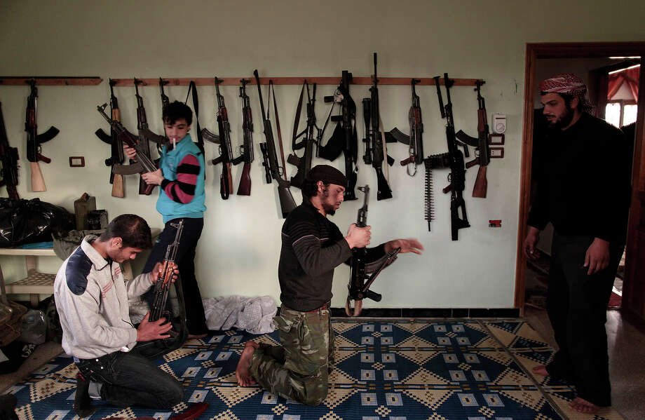 Syrian rebels clean their weapons at their headquarters in Maaret Misreen, near Idlib, Syria, Wednesday, Dec. 12, 2012. Photo: Muhammed Muheisen, ASSOCIATED PRESS / AP2012