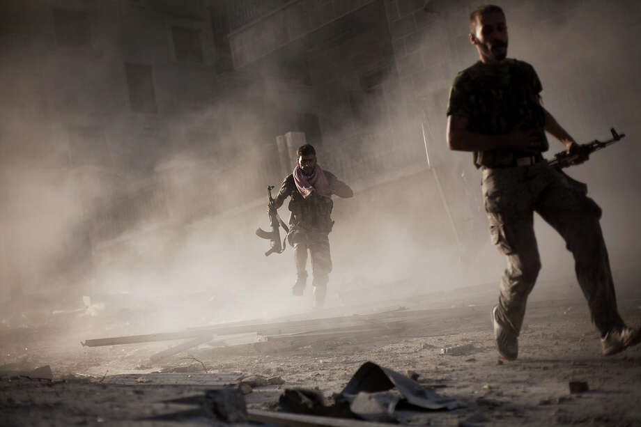 In this Friday, Sept 7, 2012 photo, Two rebel Free Syrian Army soldiers run after attacking a Syrian Army tank during fighting in the Izaa district in Aleppo, Syria.  On Friday, U.S. Senators John McCain, Joe Lieberman and Lindsay Graham, who have toured the volatile Middle East in recent days, urged Washington to help arm Syria's rebels with weapons and create a safe zone inside the country for a transition government. Photo: Manu Brabo, ASSOCIATED PRESS / AP2012