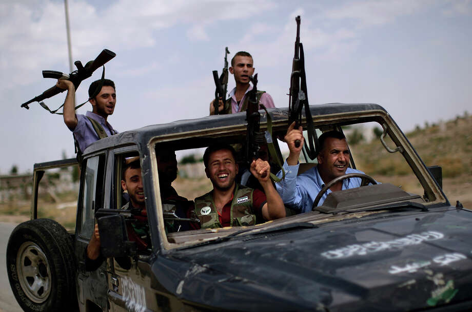Syrian rebel fighters raise their weapons as they head to fight government forces in Aleppo, in Suran, on the outskirts of Aleppo, Syria, Monday, Sept. 10, 2012. Photo: Muhammed Muheisen, ASSOCIATED PRESS / AP2012
