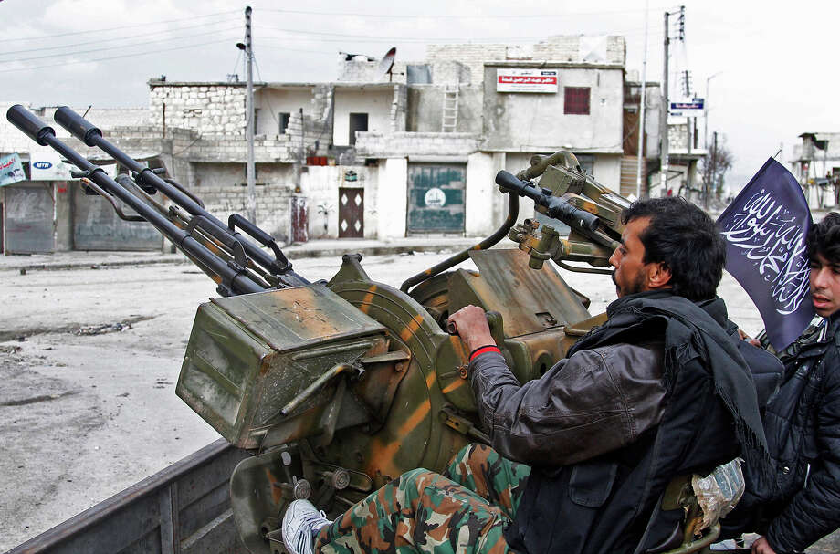 Free Syrian Army fighters sit behind their anti-aircraft weapon in Aleppo, Syria. Syrian rebels brought their fight within a mile of the heart of Damascus on Friday, seizing army checkpoints and cutting a key highway with a row of burning tires as they pressed their campaign for the heavily guarded capital, considered the likely endgame in the nearly 2-year-old civil war. Photo: Abdullah Al-Yassin, ASSOCIATED PRESS / AP2013