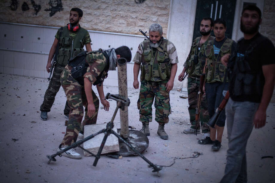 FSA soldiers prepare a mortar in Izaa district in Aleppo, Syria, Sunday, Sept. 9, 2012. On Friday, U.S. Senators John McCain, Joe Lieberman and Lindsay Graham, who have toured the volatile Middle East in recent days, urged Washington to help arm Syria's rebels with weapons and create a safe zone inside the country for a transition government. Photo: Manu Brabo, ASSOCIATED PRESS / AP2012