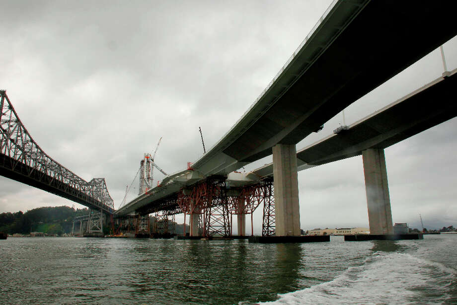 The eastern side of the old, (left) and new eastern section of the Bay Bridge as construction continues while CalTrans conducts a boat tour of the impacted areas of the bridge on Wednesday Mar. 27, 2013, in Oakland. Inspections found that 30 large bolts on the new eastern span of the Bay Bridge have fractured. Photo: Michael Macor, The Chronicle / ONLINE_YES