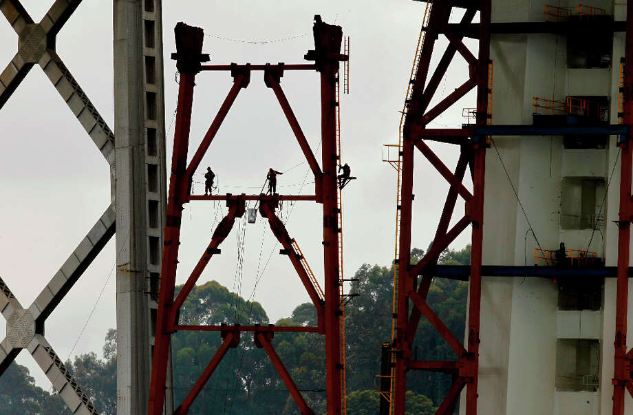 Workers continue the construction of the new eastern section of the Bay Bridge, as CalTrans conducts a boat tour of the impacted areas of new eastern section of the Bay Bridge on Wednesday Mar. 27, 2013, in Oakland. Inspections found that 30 large bolts on the new eastern span of the Bay Bridge have fractured. Photo: Michael Macor, The Chronicle / ONLINE_YES